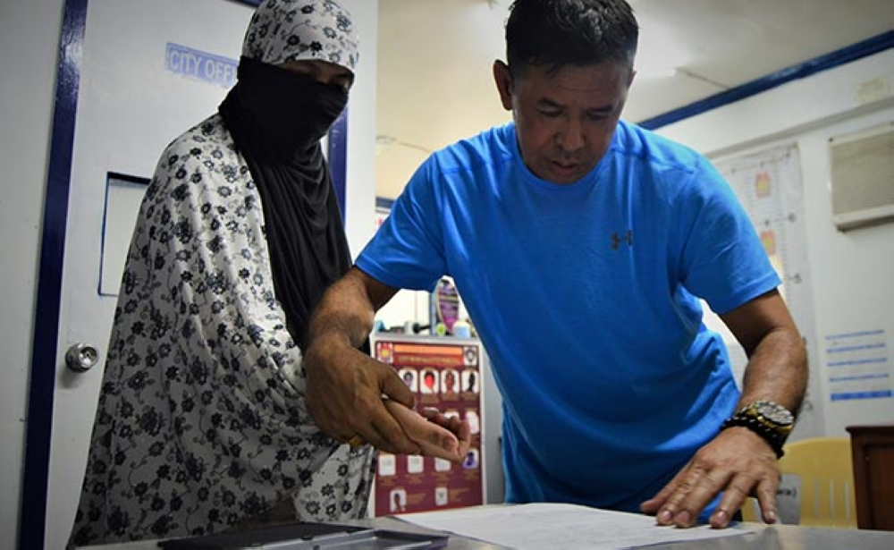 LANAO DEL NORTE. A Criminal Investigation and Detection Group (CIDG) personnel assists Junomee Dongon have her fingerprint at the CIDG office on Sunday, Feb. 25. The widow of slain terrorist Zulkifli bin Hir, alias