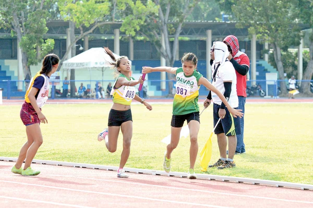 MISAMIS OCCIDENTAL. Sharon Gay Marcojos passes the baton to her teammate Andrea de Guia, the last runner, during the girls 4X400m relay final of the Batang Pinoy Mindanao Leg athletics competition that closed Friday afternoon at the Misamis Occidental Provincial Athletics Center (Mopac) in Oroquieta City. (Davao Sportswriters Association)