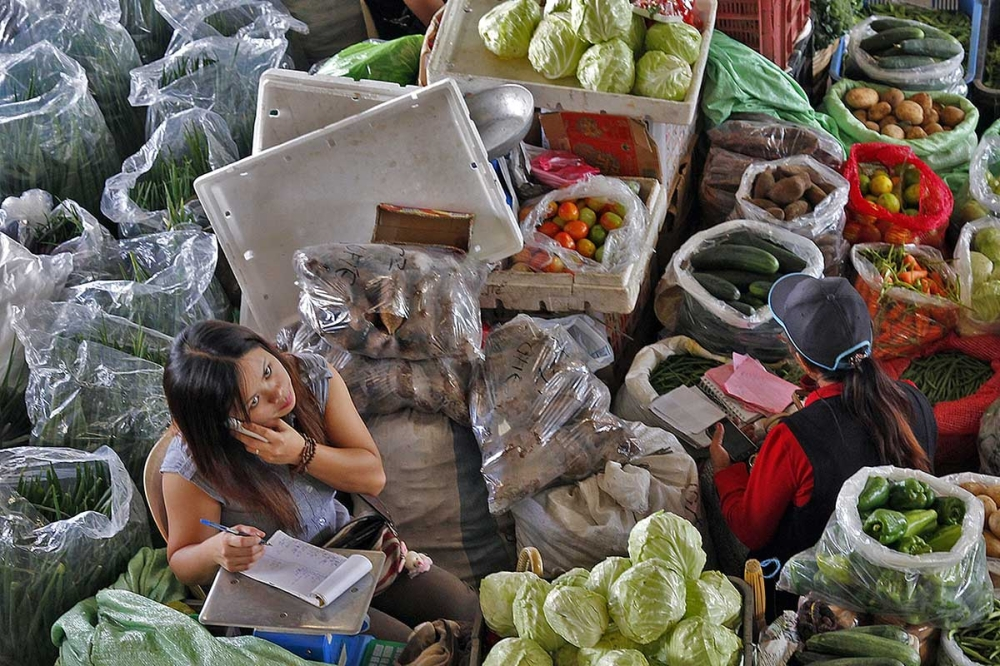 A trader takes orders of Benguet grown vegetables via her mobile phone for quicker delivery to her clients at the La Trinidad Vegetable Trading Post.