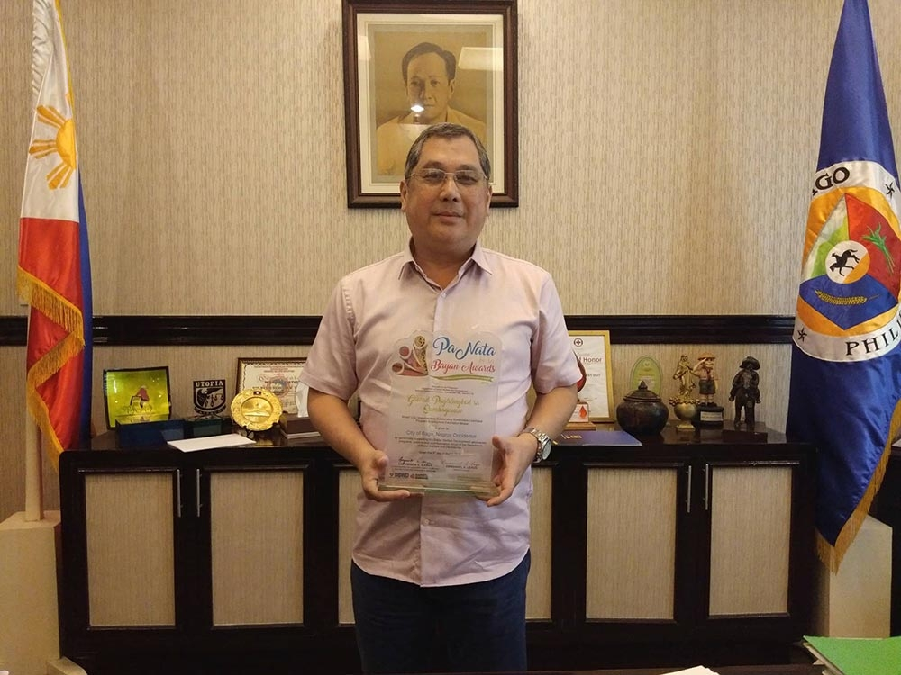 """BACOLOD. Mayor Nicholas Yulo holds the """"Gawad Paglilingkod sa Sambayanan"""" award given by the Department of Social Welfare and Development to Bago City as this year's model LGU for implementing outstanding sustainable livelihood program in the country. (Erwin P. Nicavera Photo)"""