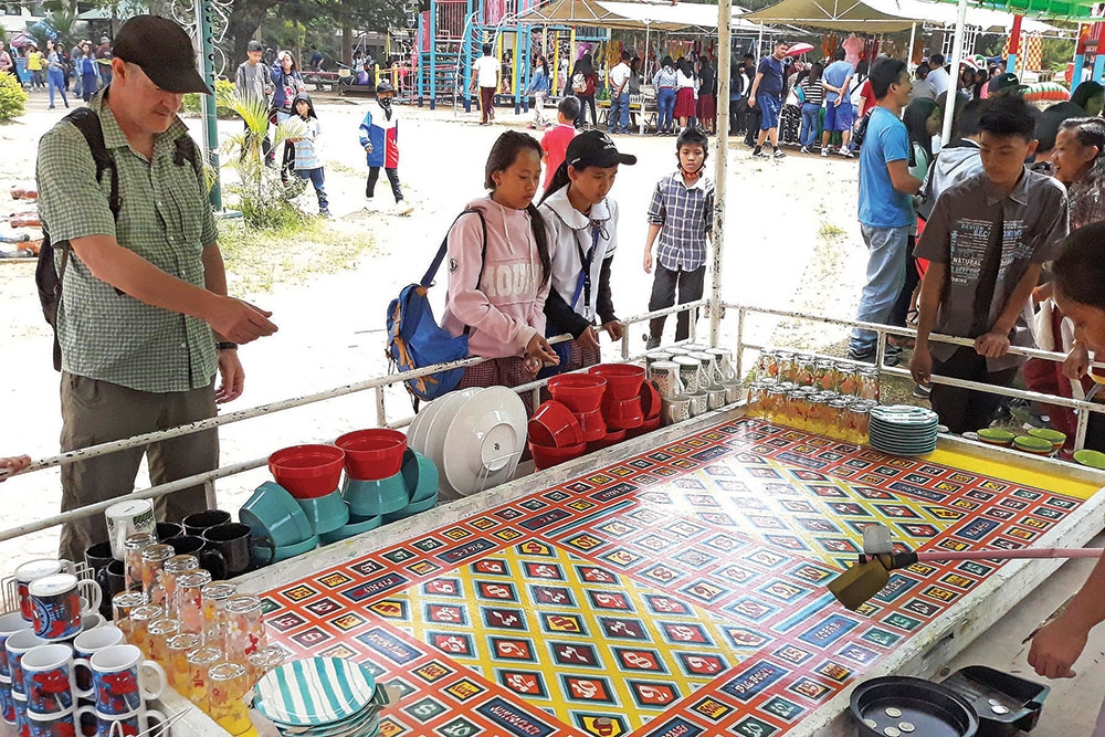 BAGUIO. Elementary, high school students and even a foreigner are enticed to play the 'piso drop' at the carnival operated at the children's playground in Burnham Park. (Milo Brioso)