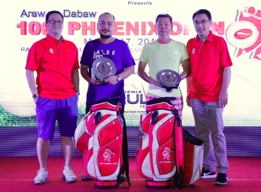 CHAMPIONS. Chris Tan (2nd from the left) and Kim Tae Jung (3rd from the left) each receive a pewter plate, a Phoenix golf bag, and Phoenix Petroleum fuel cards from Phoenix Petroleum COO Henry Albert Fadullon (rightmost) and VP for External Affairs, Business Development, and Security Atty. Raymond Zorrilla (leftmost) as overall gross champion and overall net champion, respectively, of the 10th Phoenix Open. (Contributed Photo)