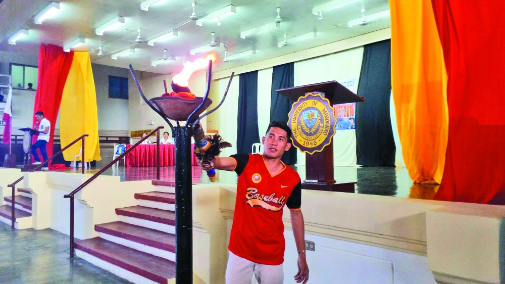 DAVAO. National Prisaa 2017 gold medalist John Wil Cadotdot lights the urn to usher the opening of the Private Schools Athletic Association (Prisaa)-Davao Meet at the University of Mindanao Tagum College gym on April 2, 2018. (Marianne L. Saberon-Abalayan)