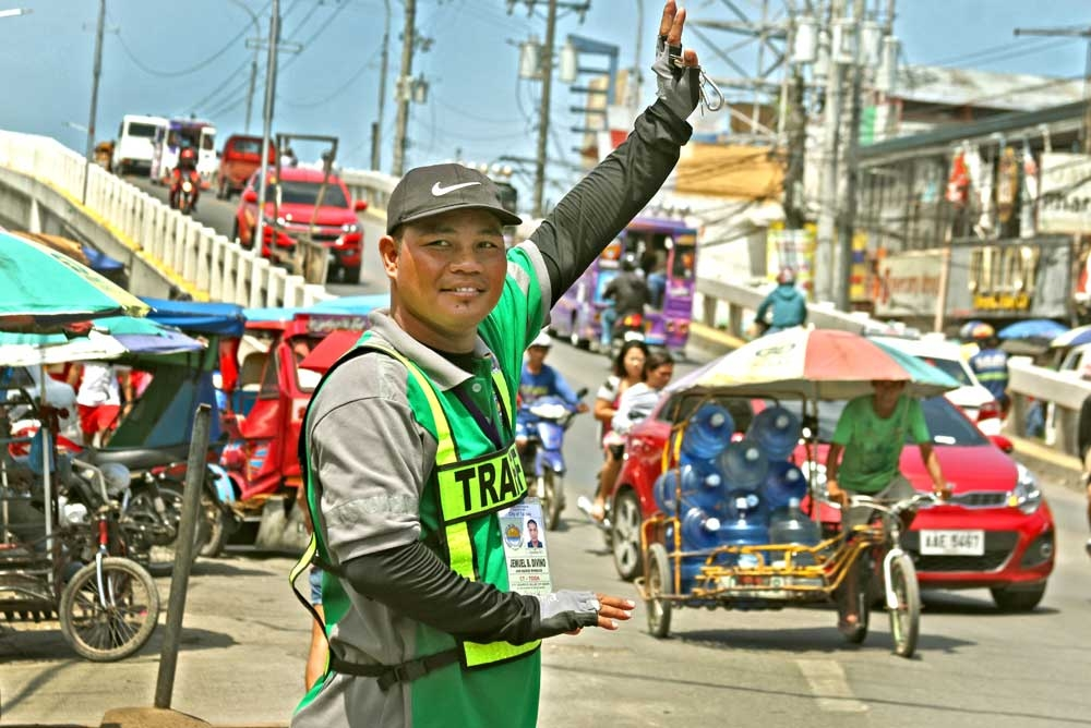 Traffic man. Boxing champ Jimrex Jaca swaps gloves for a whistle and now works as a traffic enforcer for the Talisay City Government. In photo, Jaca ensures that the traffic in Tabunok is flowing smoothly. (SunStar Photo/Alex Badayos)