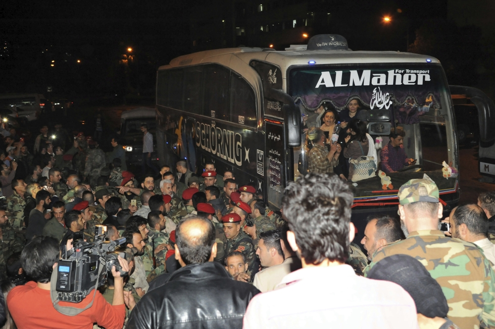 SYRIA. In this photo released by the Syrian official news agency SANA, soldiers and residents gathering near a bus carrying civilians who were released by the Army of Islam group that had been holding them since 2013, in Damascus, Syria, early Monday, April 9, 2018. Syrian state media is reporting that dozens of civilians who had been held for years by a rebel group near the capital Damascus have been freed. (AP)