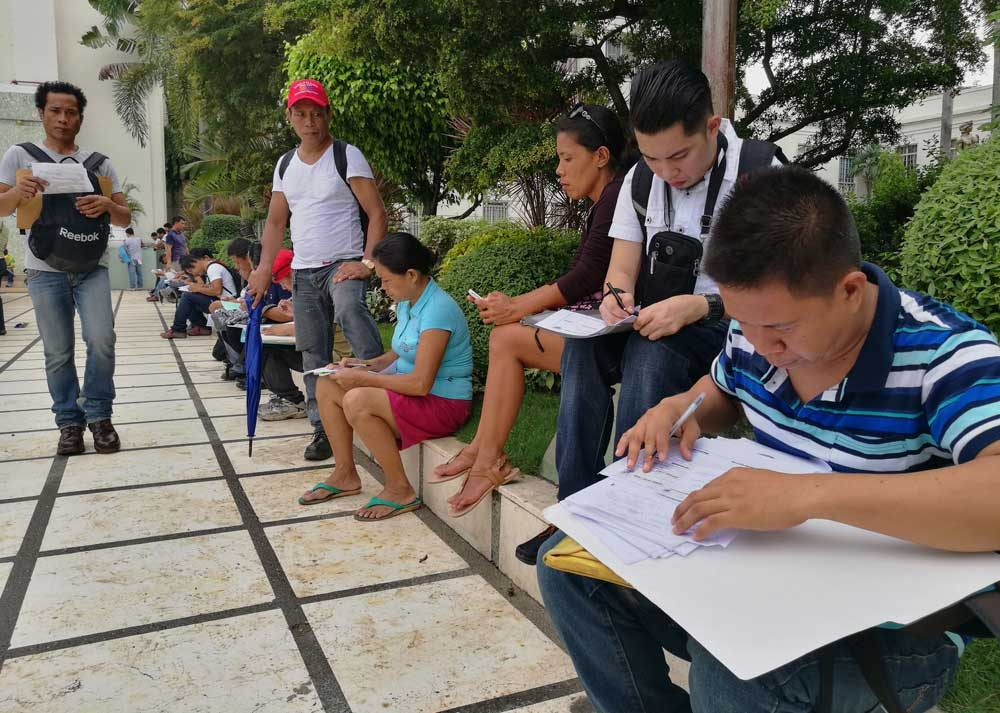 Headed overseas. Jobseekers fill out forms on the Capitol grounds at an overseas job fair. (SunStar Foto/Arni Aclao)