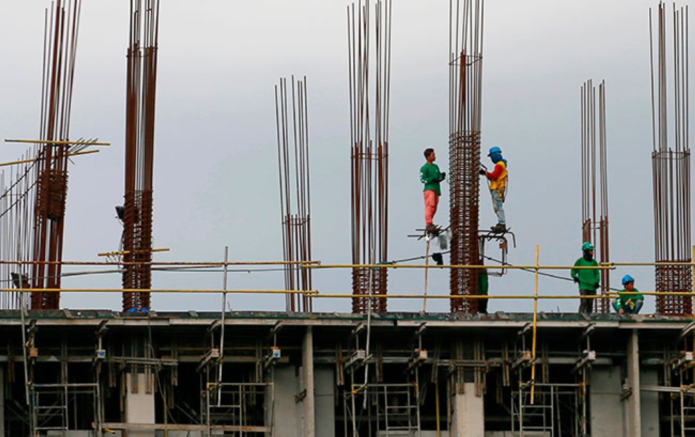 MANILA. In this January 26, 2017, file photo, construction workers stand on the scaffolding around metal rods of a new pillar as they build more floors at a reclamation site in Paranaque City, south of Manila, Philippines. (AP)