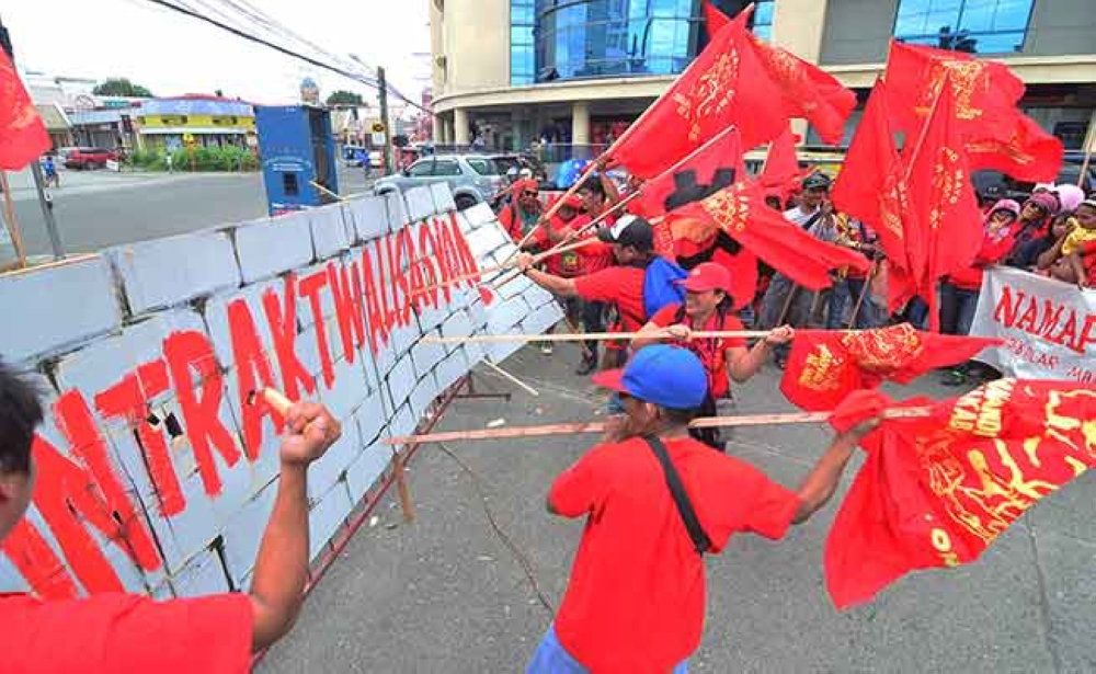 DAVAO. Protesters try to take down a banner with the word