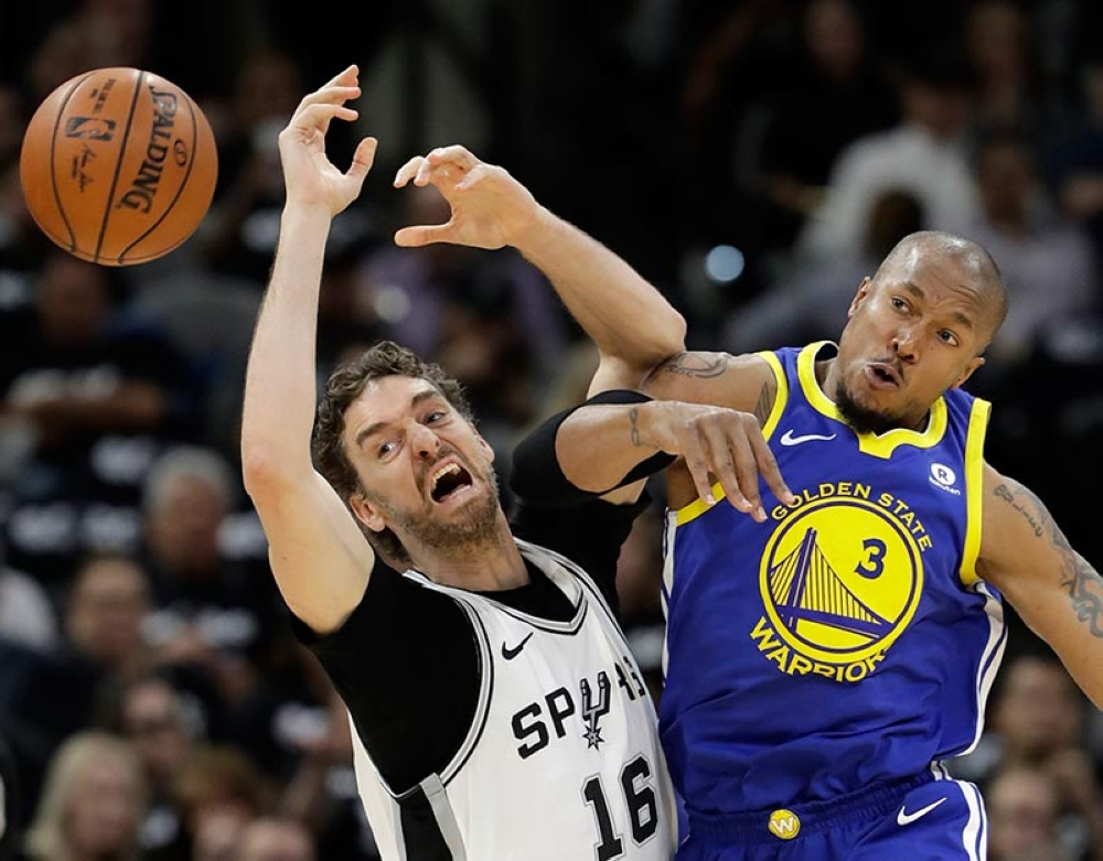 SAN ANTONIO. The ball goes flying as San Antonio Spurs' Pau Gasol (16) and Golden State Warriors' David West (3) compete for control of it during the first half of Game 3 of a first-round NBA basketball playoff series in San Antonio, Thursday, April 19, 2018. (AP)