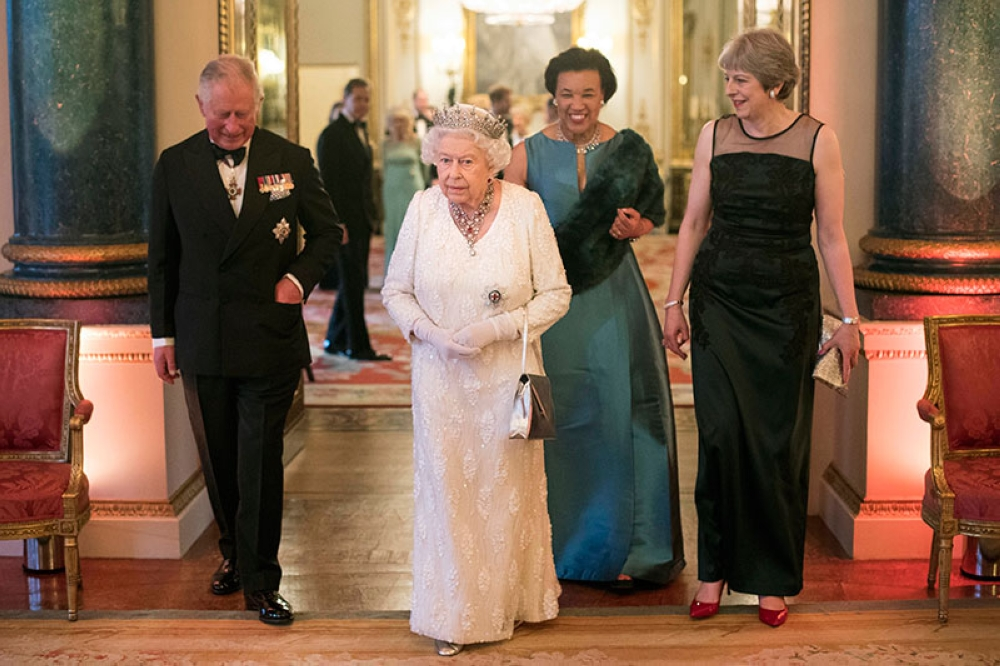 LONDON. Britain's Queen Elizabeth II, Prince Charles, Commonwealth Secretary-General Patricia Scotland and Prime Minister Theresa May walk in the Blue Drawing Room at Buckingham Palace as the Queen hosts a dinner during the Commonwealth Heads of Government Meeting, in London, Thursday April 19, 2018. (AP)