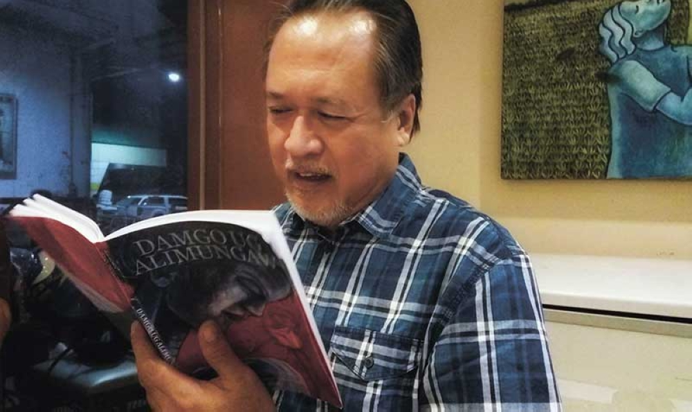 NEW BOOK. Poet-diplomat Vicente Vivencio Bandillo checks on his book that he will be launching this Friday, April 27. (Contributed photo)