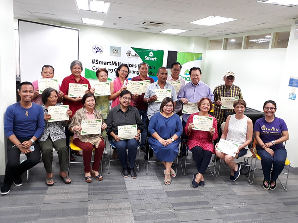 Senior citizens pose after receiving their certificates for finishing the Smart