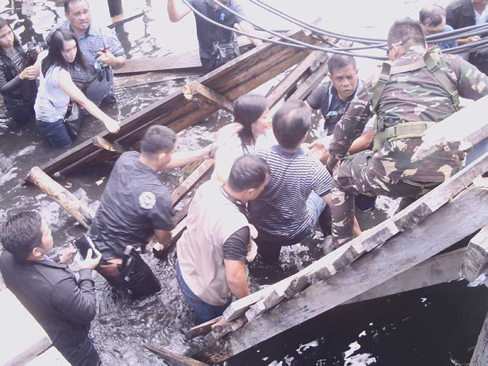 ZAMBOANGA. A soldier of Task Force Zamboanga assists Mayor Maria Isabelle Climaco-Salazar (in white shirt) and Negros Occidental 3rd District Rep. Alfredo Abelardo Benitez (in striped shirt) after the wooden stilt-bridge they were on collapsed Thursday, April 26, 2018. (Bong Garcia)