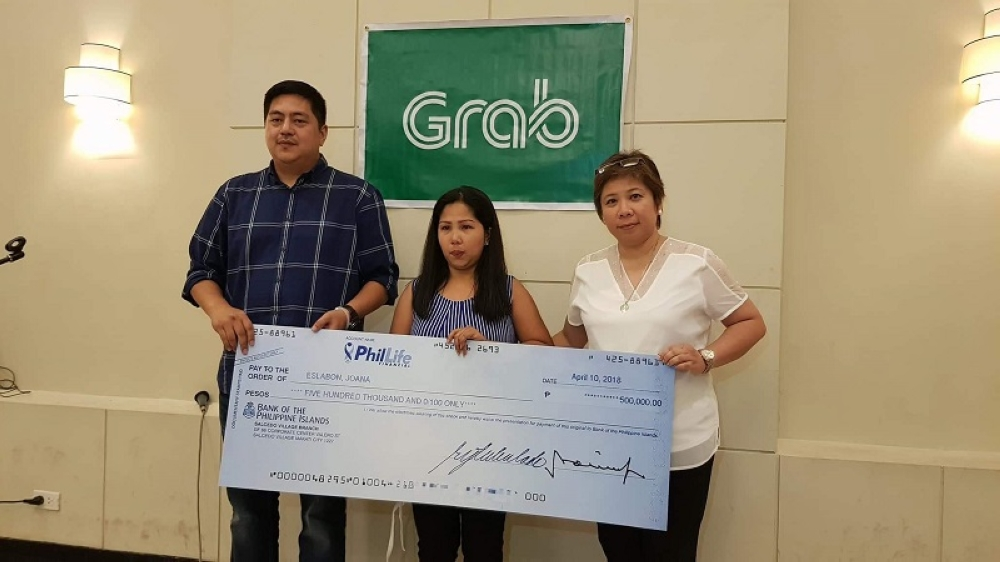 BACOLOD. Wayne Jacinto, head of driver services and community management of Grab, and Jocelyn Yoshida, Grab Bacolod manager, turn over the check to Joanna Eslabon, whose husband died due to cardiac arrest on January 1 this year. (Carla Cañet)