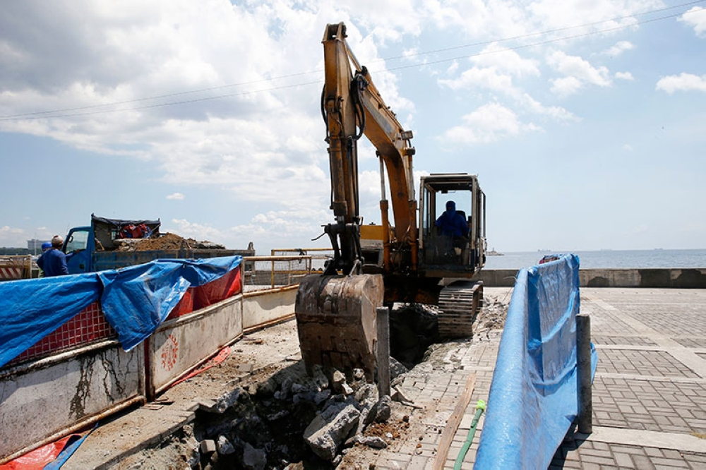 MANILA. A backhoe scoops earth from the spot where a statue of a