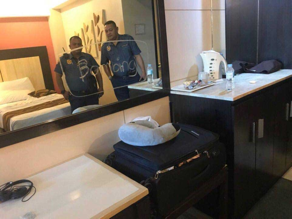 """No joking matter. Police officers check the hotel room where an Australian national had written the word """"bombing"""" on the mirror. (Contributed Foto)"""