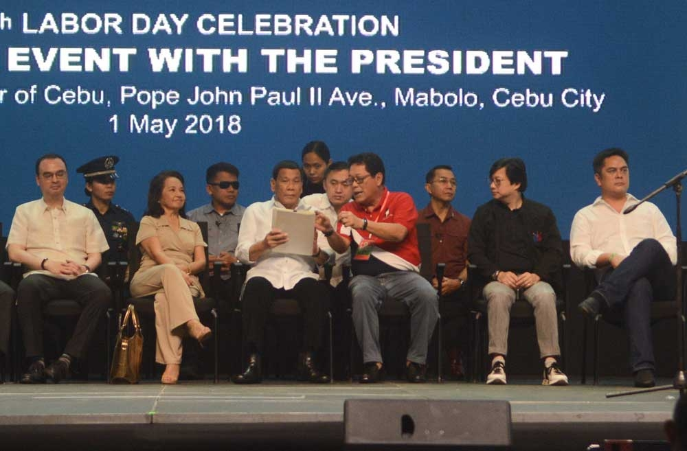 Signed, sealed. President Rodrigo Duterte receives a copy of the executive order from Labor Secretary Silvestre Bello III. With them in the Labor Day celebration in Cebu City are (front,  from left) Foreign Affairs Secretary Alan Peter Cayetano, Rep. Gloria Macapagal-Arroyo, Presidential Assistant Michael Dino, and PCOO Secretary Martin Andanar. (SunStar Foto/Arni Aclao)