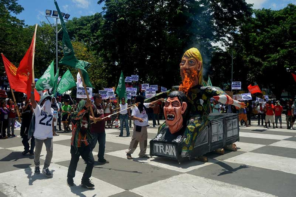 BACOLOD. Protesters burn the effigy of Philippine President Rodrigo Duterte and United States President Donald Trump during the Labor Day rally at the Bacolod City public plaza. (Marchel P. Espina