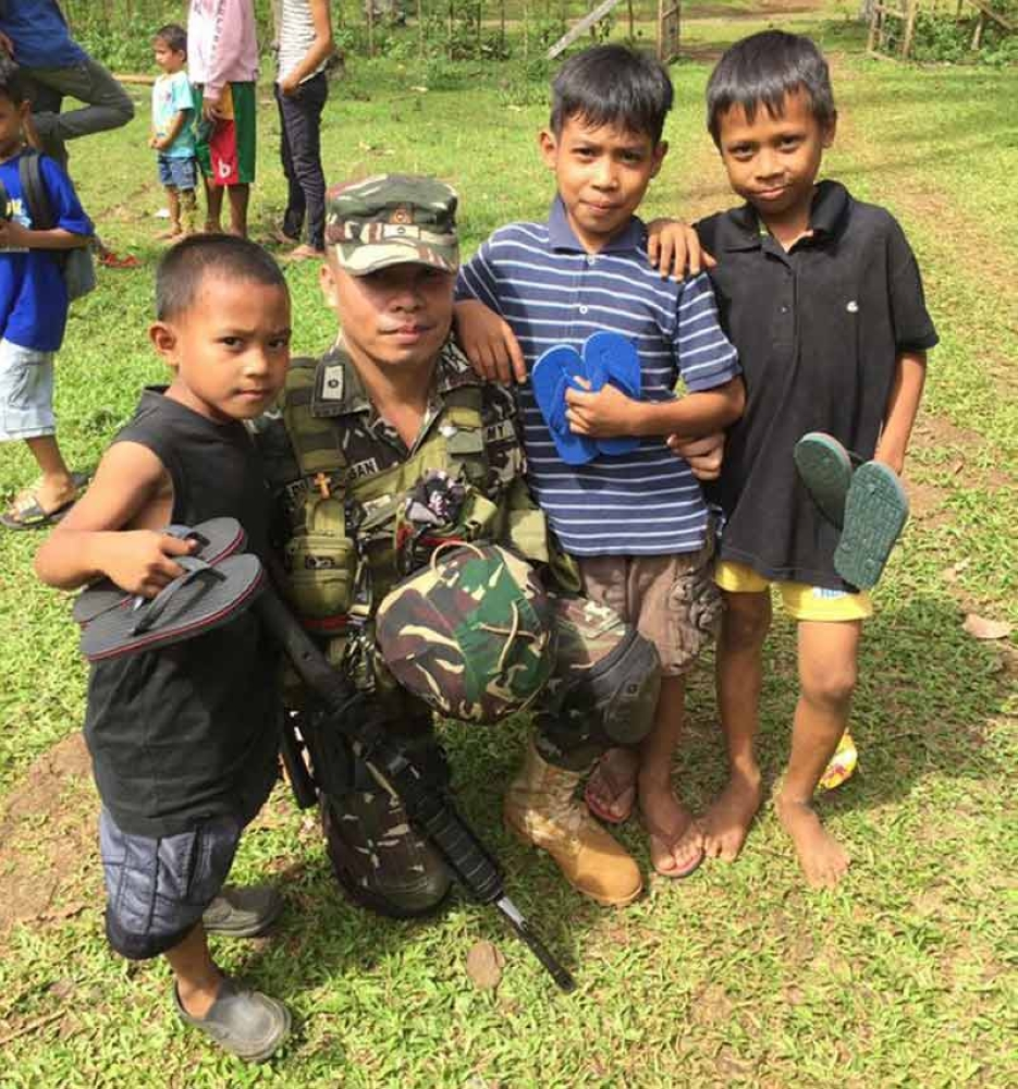 Army Major Arturo Dumalagan spends time with the school children who received slippers from their advocacy group. (Photo courtesy of