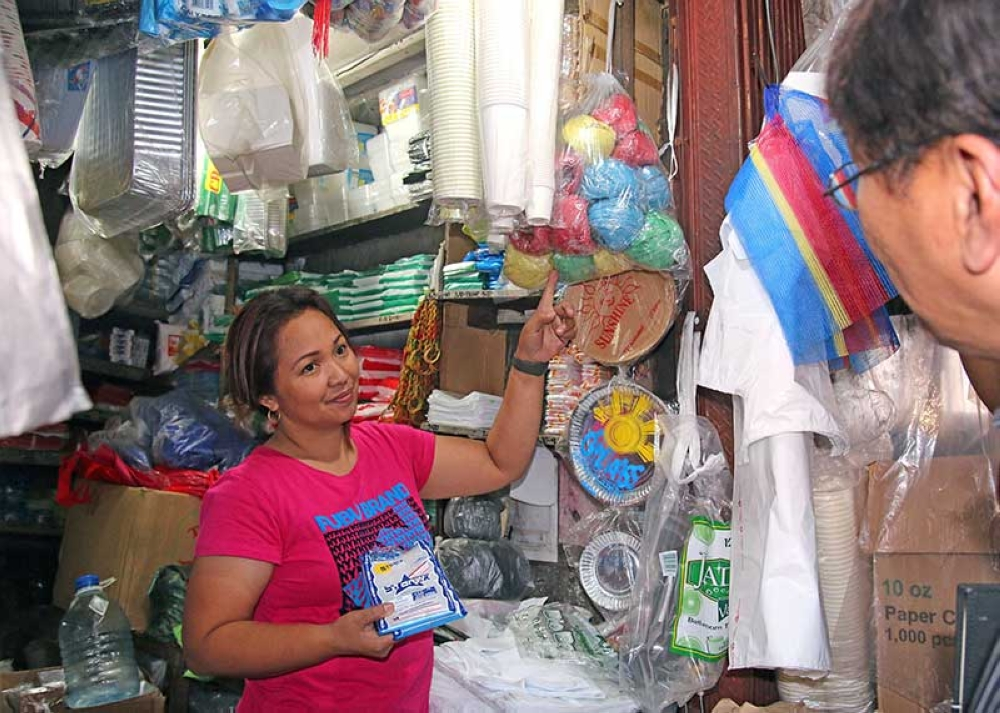 BAGUIO. A city official checks on a vendor at the city market while giving out further information prohibiting the use of plastic and styrofoam products in the Summer Capital. (Milo Brioso)