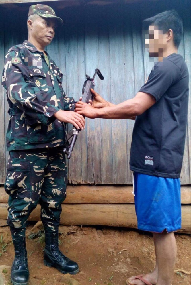 NPA surrenderee hands his AK47 rifle to a military officer in Malitbog, Bukidnon. (4ID photo)