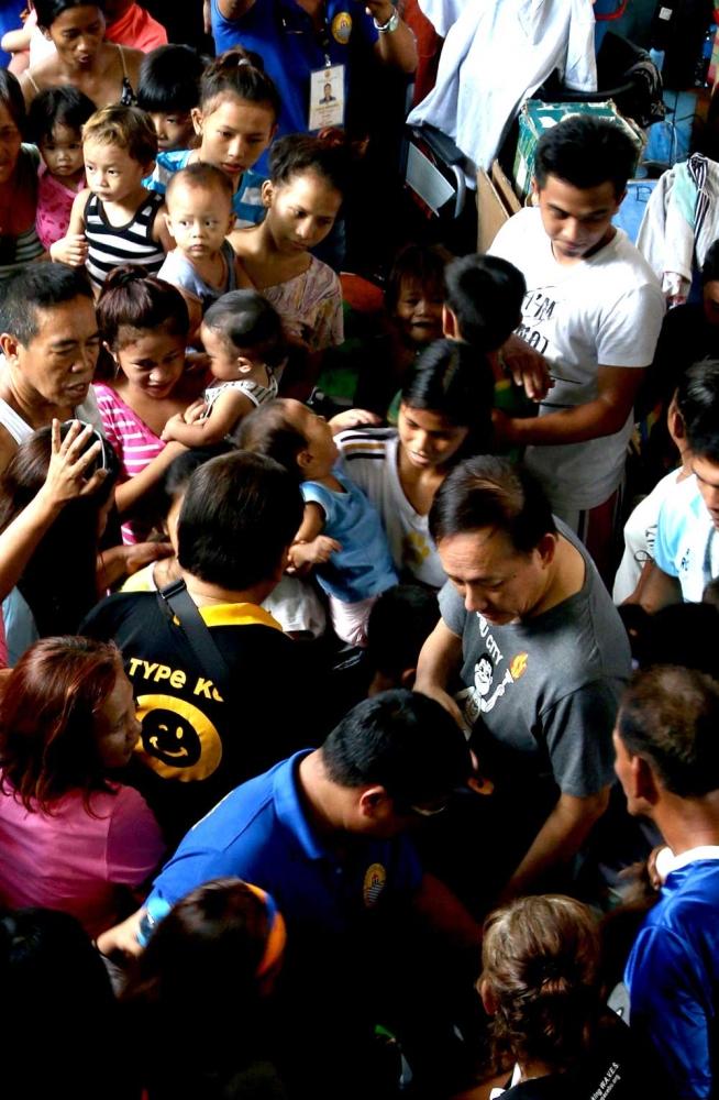 Crowd.  Cebu City Mayor Tomas Osmeña (back to camera, with Type O shirt) and Councilor Joy Augustus Young visit a temporary shelter for fire survivors in Barangay Ermita. (SunStar Photo/Alex Badayos)