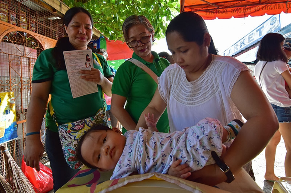 A mother lowers her baby to an electronic weighing scale as part of their weekly check-up at Barangay Hall of Agdao Proper in Davao City. (Macky Lim)