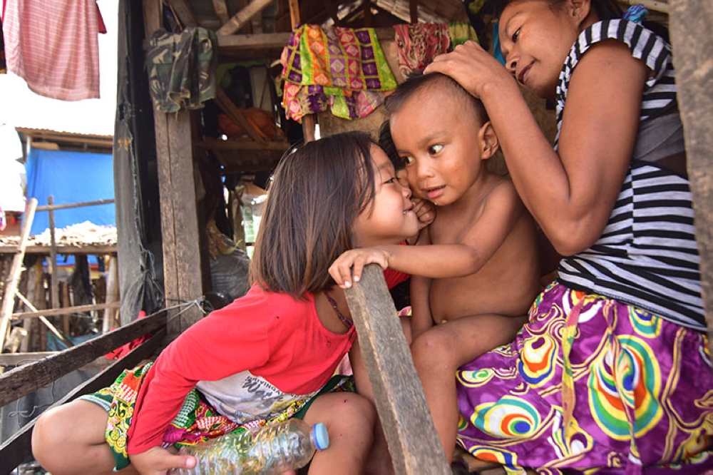 A girl plays with her younger brother while their mother looks after them at Barangay 23-C Isla Verde Boulevard, Davao City. (Macky Lim)