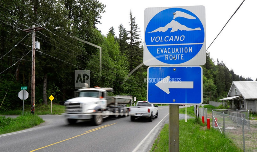 WASHINGTON. In this May 8, 2018 photo, a volcano evacuation route sign directs traffic and pedestrians to an area of higher ground near Orting, Wash. should nearby Mount Rainier erupt or trigger a lahar mud flow. The eruption of the Kilauea volcano in Hawaii has geologic experts along the West Coast warily eyeing the volcanic peaks in Washington, Oregon and California, including Rainier, that are part of the Pacific Ocean's ring of fire. (AP Photo)