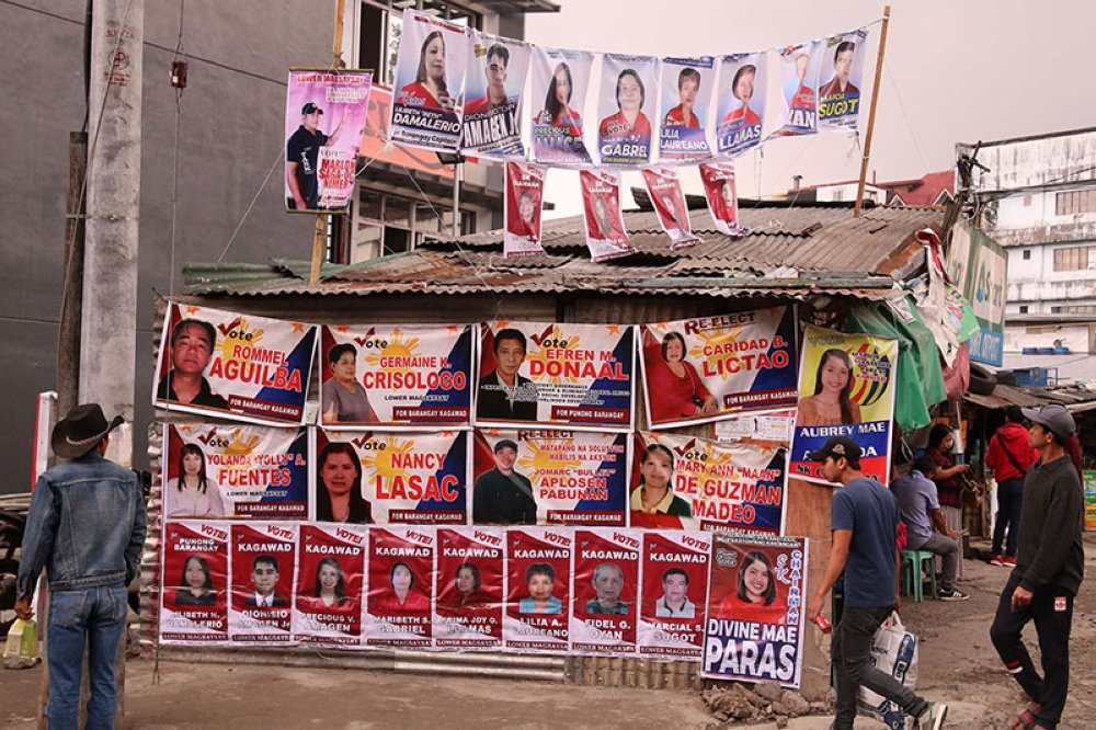 BAGUIO. Voters take a last look at campaign posters in one of the barangays in Baguio City as they head to the different polling precincts today, May 14, for the synchronized Barangay and Sanguniang Kabataan elections. (Photo by Milo Brioso)