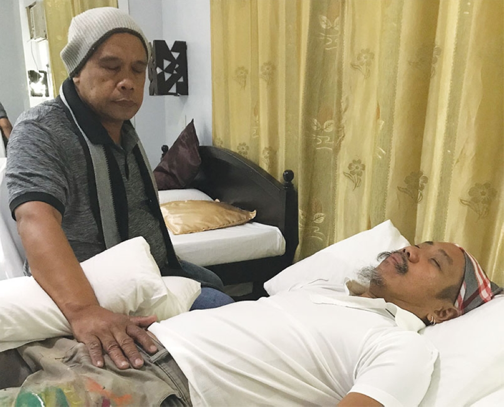 HEALING FOR ALL. While of Islamic faith, Warka Adala counts among his patients Catholic priests and nuns and medical practitioners. Here, he attends to this writer's mother and artist Kublai Millan during his first day of healing at Ponce Suites in Davao City. (Stella Estremera)