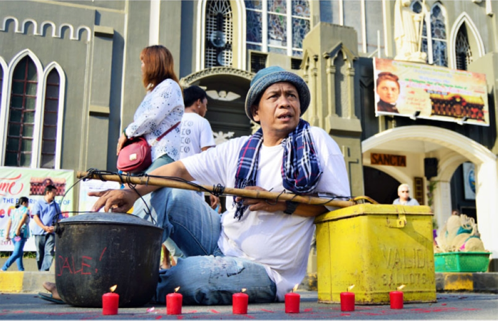 CAGAYAN DE ORO. With a cooking pot and a ballot box as his main props,  local artist Nicolas Aca stages a performance art outside the St. Augustine Metropolitan Cathedral in Cagayan de Oro, hoping to catch the attention of the Roman Catholic devotees not to sell their votes.	 (Jigger J. Jerusalem)