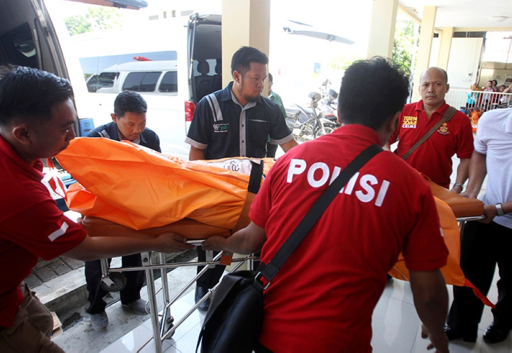 INDONESIA. Police officers carry a body bag containing one of the victims of Sunday's explosions upon arrival at a hospital in Surabaya, East Java, Indonesia, Monday, May 14, 2018. (AP)