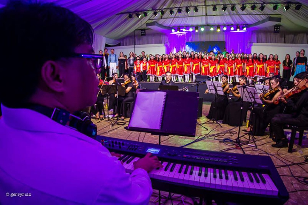"""TACLOBAN. Melvin Corpin, a multi-awarded composer and liturgical hymn maestro in the Philippines, leads the choir during the """"Kabilin Concert"""" with the Waraynon Initiative Network (WIN) last July 1-2, 2017 at the RTRMF  Gymnasium in Tacloban City. (Photo courtesy of Gerry Ruiz)"""