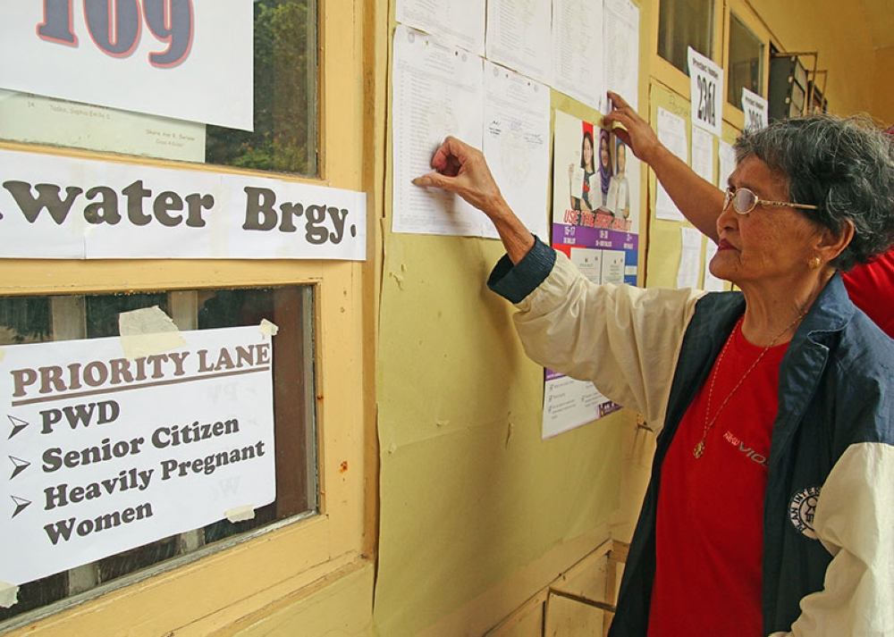 BAGUIO. A senior citizen looks for her name in one of the polling precincts during the Barangay and SK Elections on May 14. (Milo Brioso)