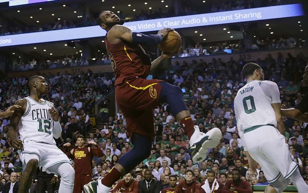 Cleveland Cavaliers forward LeBron James, center, recoils after colliding with Boston Celtics forward Jayson Tatum, right, in front of Celtics guard Terry Rozier, left, during the first half in Game 2 of the NBA basketball Eastern Conference finals Tuesday, May 15, 2018, in Boston. (AP Photo/Charles Krupa)
