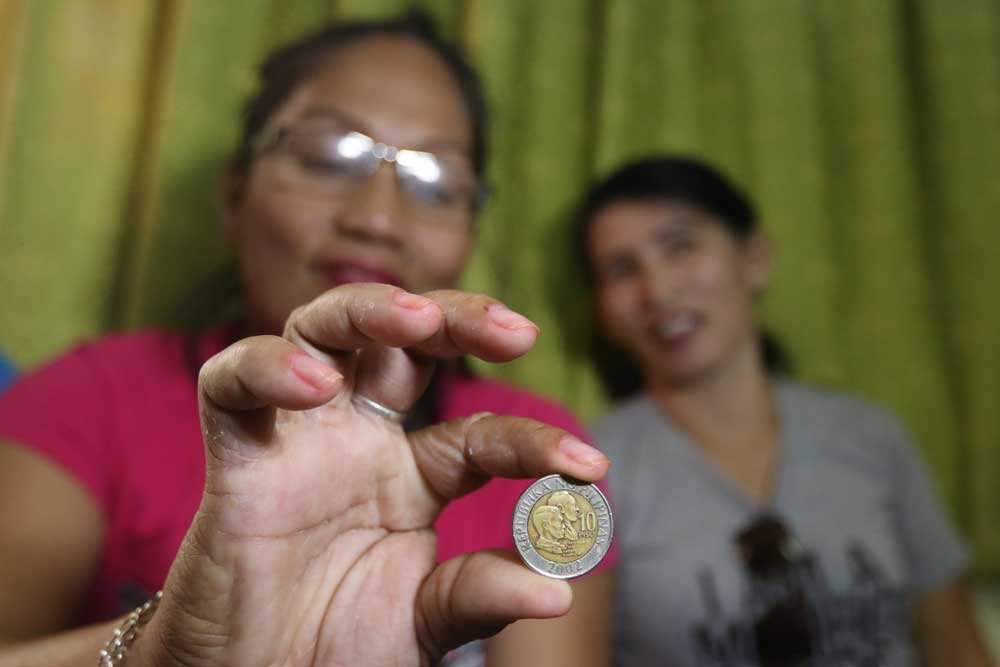 A souvenir. Alicia Alcoseba shows the P10 coin, its head side, that gave her the seventh seat in the barangay council of Lantawan, San Fernando. Yesterday, a coin toss broke the tie between her and her friend Analyn Illustrisimo, who also got 515 votes.  (SunStar Photo/Alex Badayos)