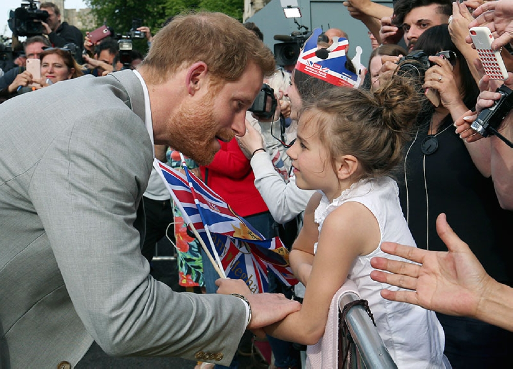 ENGLAND. Britain's Prince Harry, left, greets a young well-wisher during a walkabout with Prince William outside Windsor castle, in Windsor, England, Friday, May 18, 2018 ahead of Prince Harry's wedding to Meghan Markle on Saturday. (AP)