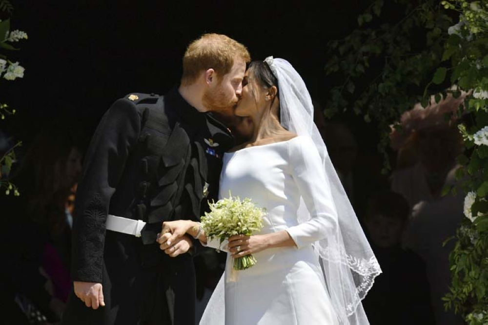 Britain's Prince Harry and Meghan Markle kiss as they leave after their wedding at St. George's Chapel in Windsor Castle in Windsor, near London, England, Saturday, May 19, 2018.(AP)