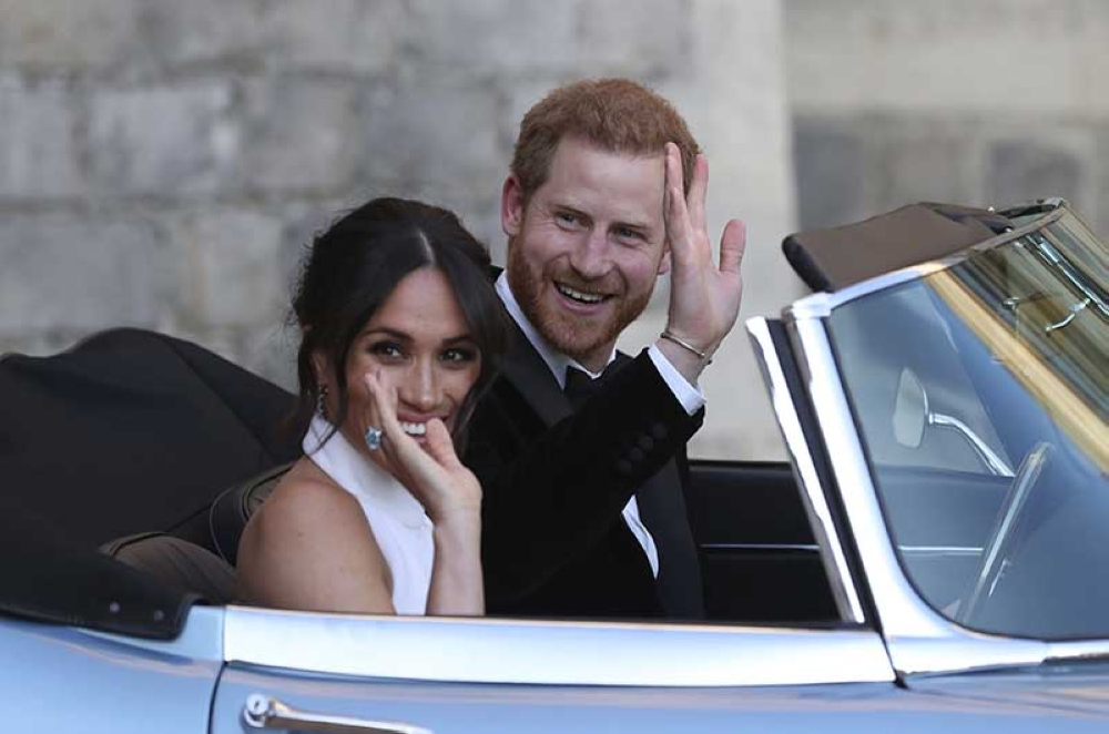 LONDON. The newly married Duke and Duchess of Sussex, Meghan Markle and Prince Harry, leave Windsor Castle in a convertible car after their wedding in Windsor, England, to attend an evening reception at Frogmore House, hosted by the Prince of Wales, Saturday, May 19, 2018. (AP Photo)