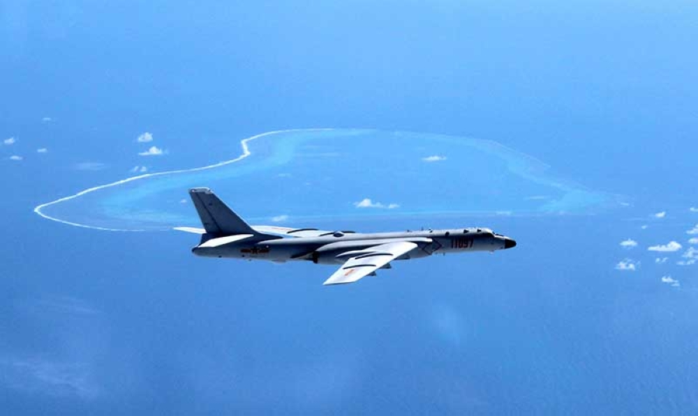 In this undated file photo released by Xinhua News Agency, a Chinese H-6K bomber patrols the islands and reefs in the South China Sea. The China Daily newspaper reported Saturday, May 19, 2018 that People's Liberation Army Air Force conducted takeoff and landing training with the H-6K bomber in the South China Sea. (AP File Photo)