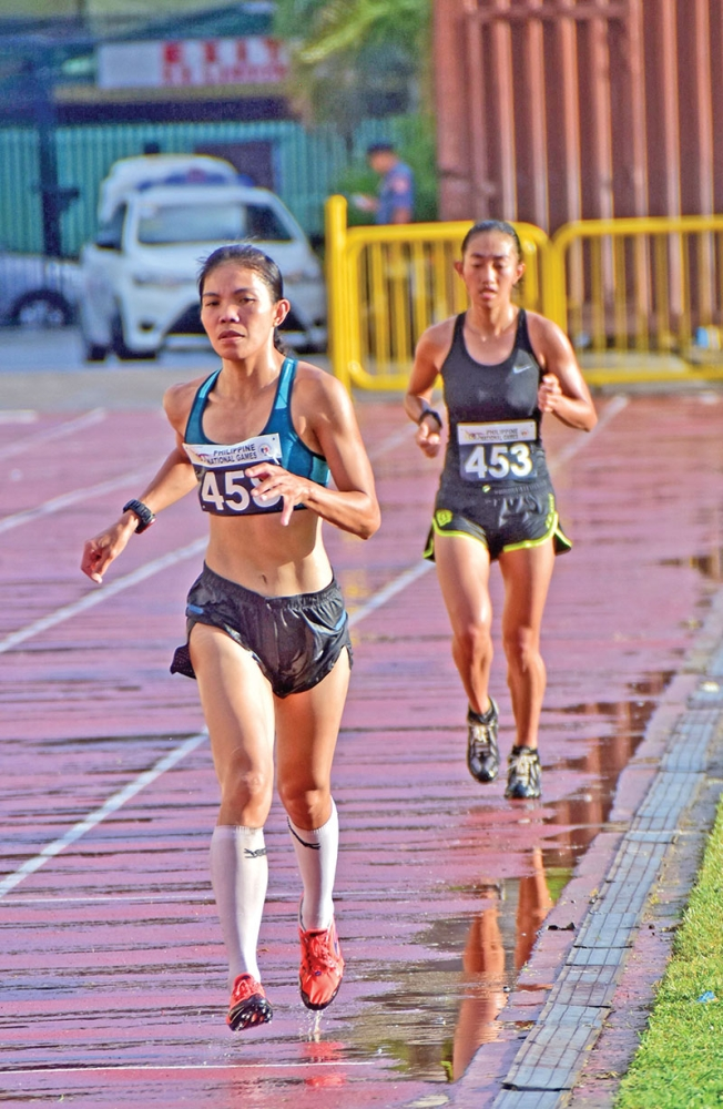 FIRST GOLD. Christable Martes of Baguio City races past her rival to win the  gold medal of the women's 10,000-meter run, the first finals event of the Philippine National Games 2018 athletics competition at the Cebu City Sports Center yesterday. (Macky Lim)
