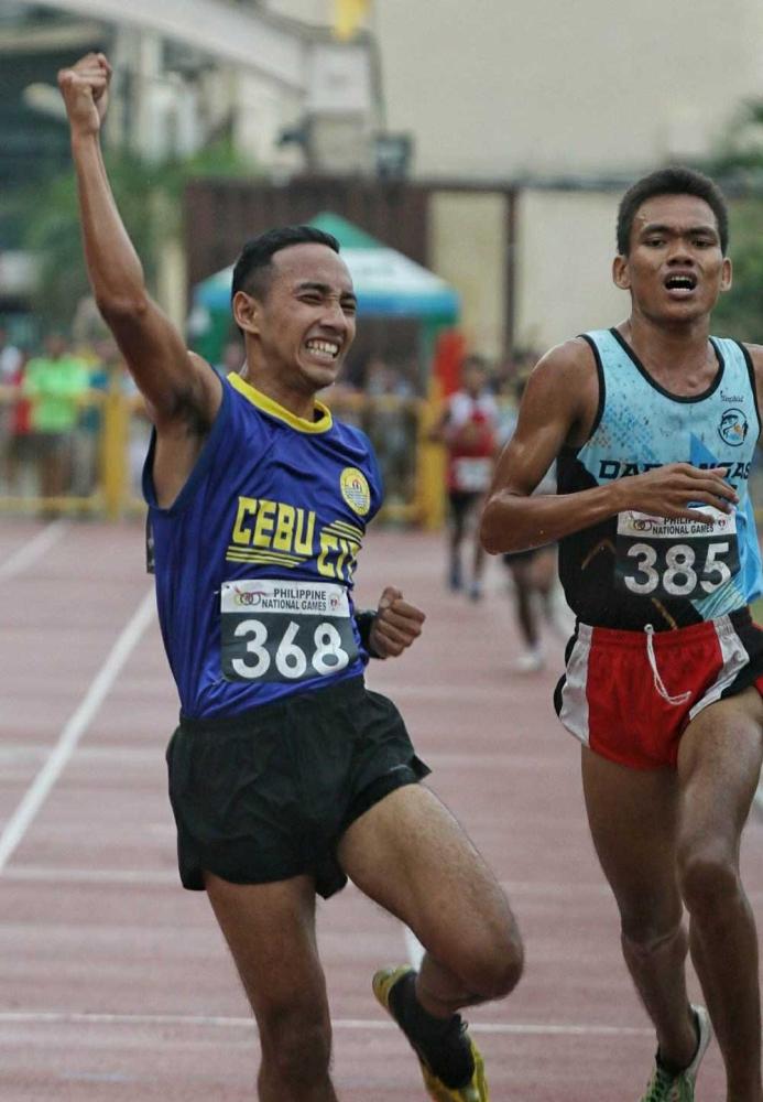 Double gold. Si Prince Joey Lee (wala) nagselebrar human niya malangkat ang iyang ikaduhang gold sa 5,000 meter run. Sa sayo pa, siya usab ang nanghawod sa 10,000 meter run senior boys division. (Alex Badayos)