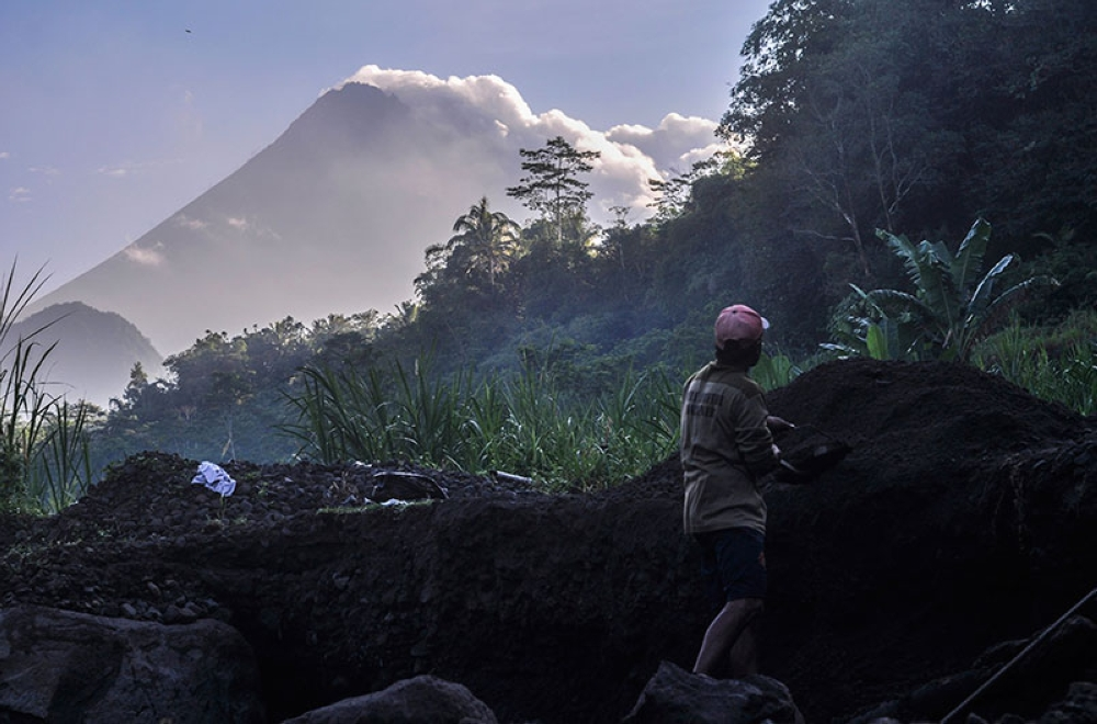 INDONESIA. A man works at a sand mining site as Mount Merapi is seen in the background in Yogyakarta, Indonesia, Tuesday, May 22, 2018. (AP)