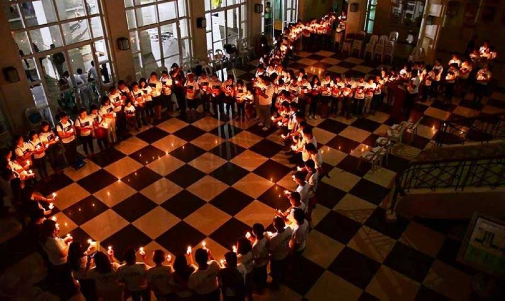 CANDLE-LIGHTING. Participants from the Bacolod City government and other organizations light candles at the Government Center Monday to mark the 35th International Aids Candle-light Memorial. (Bacolod City PIO Photo)