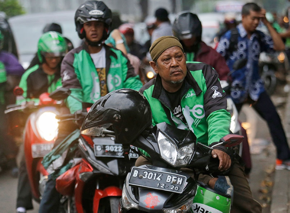 INDONESIA. In this April 29, 2016, file photo, Go-Jek motorcycle taxi drivers wait for customers in Jakarta, Indonesia. (AP)