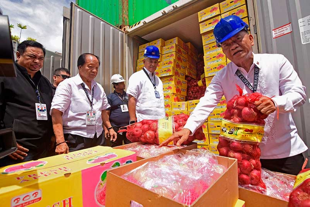 DAVAO. District Collector lawyer Romalino Valdez and Customs Commissioner Isidro Lapeña inspects shipments declared to contain apples but actually contain onions inside. (Mark Perandos)