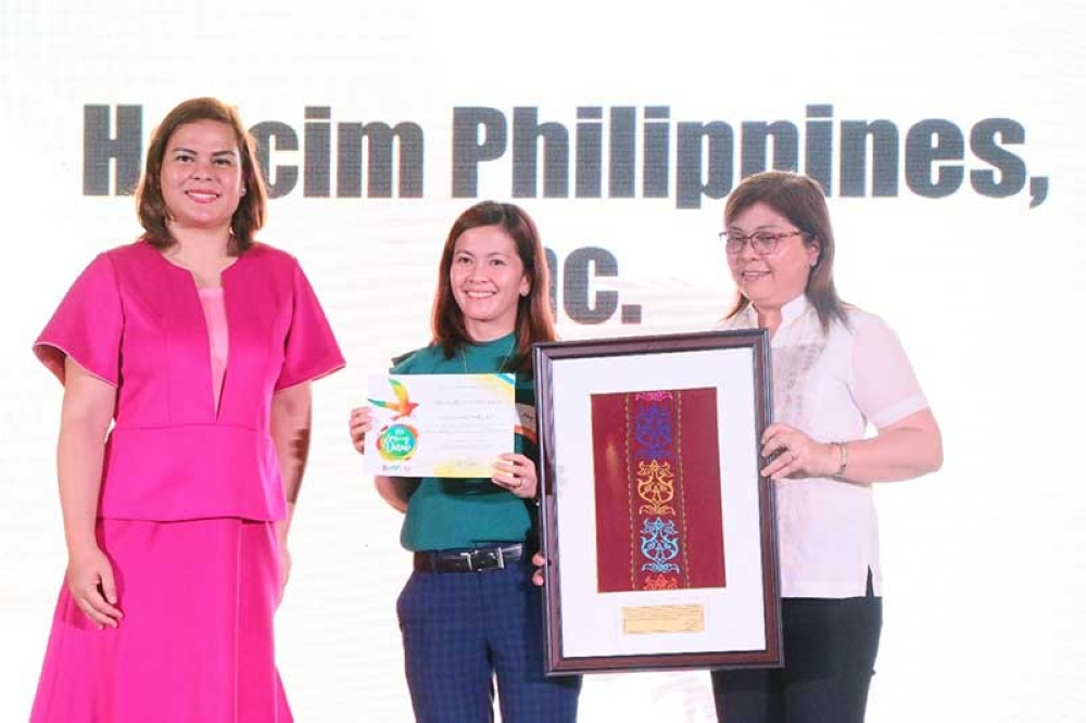 DAVAO. Holcim Davao Corporate Social Responsibility manager May Escalicas (middle) receives a plaque from Davao City Mayor Sara Duterte-Carpio (left) recognizing the plant's social programs during the Pasidungog Festival.