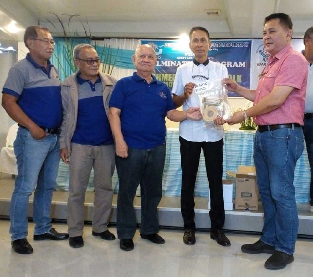 ZAMBOANGA. BFAR Regional Director Isidro Velayo, Jr. (1st from right) joins SOPHIL executive vice president Roberto Baylosis (center) on Thursday in the distribution of fishing gears for free, which is part of the corporate social responsibility of SOPHIL. (Bong Garcia)