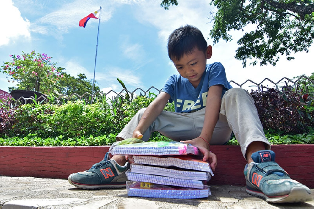 DAVAO. A young boy checks the stack of school supplies being distributed on Thursday morning, May 31, at the Davao City Hall in preparation for the opening of classes next week. The distribution of free school supplies by the City Government of Davao will continue today. (Macky Lim)